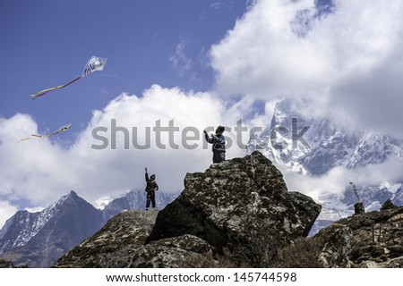 KHUMJUNG,NEPAL-APRIL 01:Young unidentified kids flying a kites on the background of Ama Dablam(6814 m) at Khumjung Village on April 01,2012 in the Himalaya Everest Region,Nepal