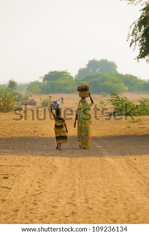 KHURI, INDIA - NOVEMBER 26: An Indian mother and daughter fetch water at the rural community well with balanced jugs in the dry desert climate on November 26, 2009 in Khuri, India - stock photo