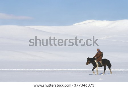KHUSTAIN NURUU , MONGOLIA - 02-05-2008 ; Mongolian woman in wintertime is riding her horse in a beautiful snow landscape