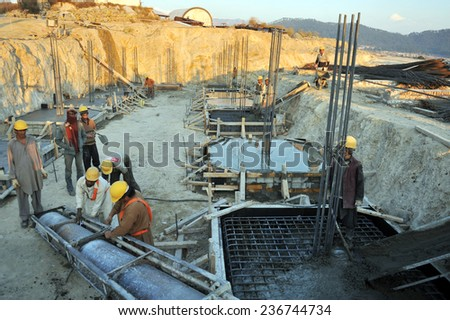 KHYBER PAKHTUNKHWA, PAKISTAN - JAN 21: Labours busy in construction work of a building  on January 21, 2011 in Khyber Pakhtunkhwa, Pakistan. - stock photo