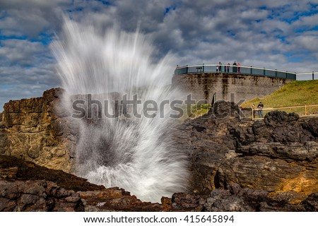 KIAMA,AUSTRALIA - APRIL 24, 2016: Tourists watch as the famous Kiama Blowhole erupts. The world's largest, it attracts close to 1m visitors every year. - stock photo