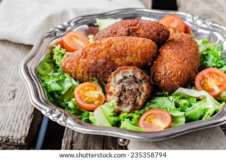 Kibbeh - Arabian trsditional meatballs,  minced meat and bulghur wheat fried snack with green salad in iron vintage plate on wooden background. Eastern cuisine - stock photo