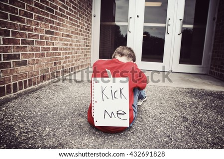 Kick me sign on a childs back, bullying concept