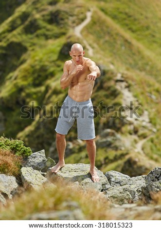 Kickboxer or muay thai fighter practicing shadow boxing on a mountain