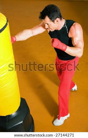 Kickboxer punching the sandbag - stock photo
