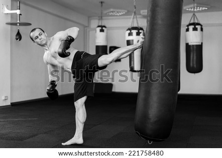 Kickboxer training in the gym kicking the punch bag - stock photo