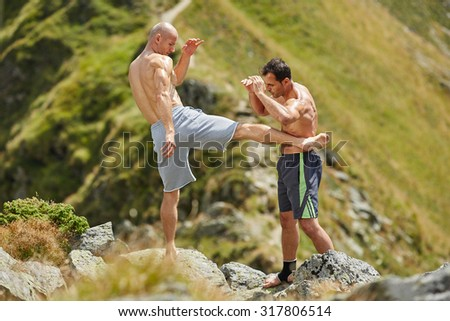 Kickboxers or muay thai fighters training in the mountains, sparring