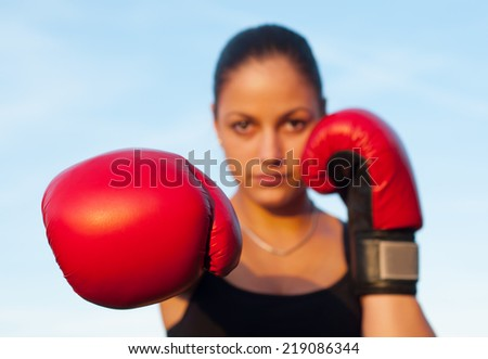 Kickboxing girl exercising in the nature on sunny summer day. - stock photo