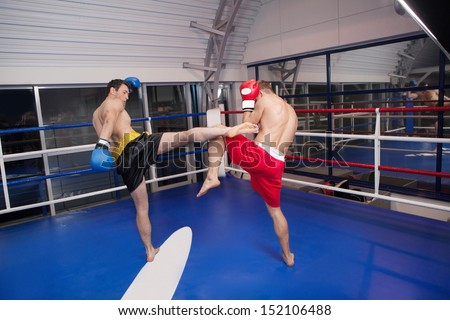 Kickboxing. Two confident men kickboxing on the ring - stock photo