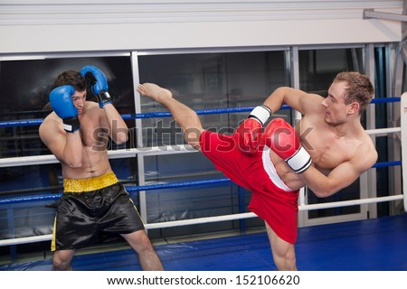 Kickboxing. Two young men kickboxing on the ring - stock photo