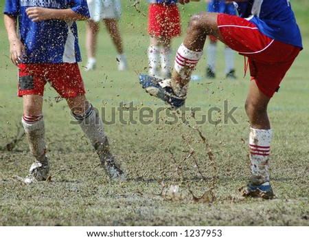 Kicking in the mud (Soccer) - stock photo