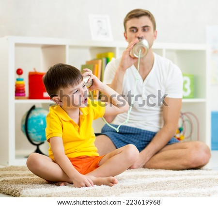 Kid and dad having a phone call with tin cans - stock photo