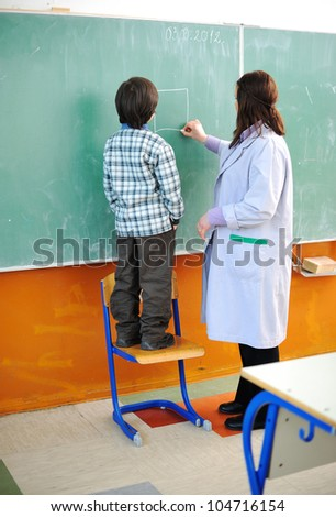 Kid and his teacher in classroom - stock photo