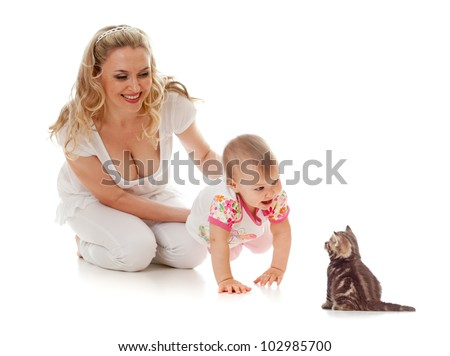 Kid and loving mother; girl steps on her hands forward to small kitten - stock photo