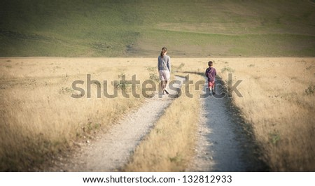 Kid and mother walking outdoors. Castelluccio di Norcia, Monti Sibillini Park, Italy.