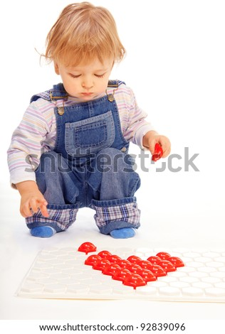 Kid assemble a mosaic in form of hearts before Valentine day - stock photo