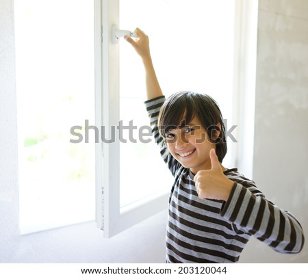 Kid at home by the window - stock photo