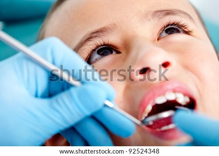 Kid at the dentist getting his teeth checked - stock photo