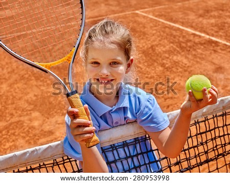 Kid athlete in blue form with racket and ball on  brown tennis court. - stock photo