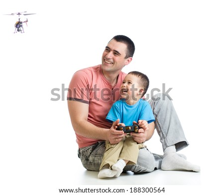 Kid boy and dad playing with RC helicopter toy - stock photo