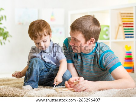 Kid boy and father play with toys on the floor at nursery