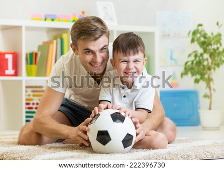 kid boy and father playing with soccerball  indoor - stock photo