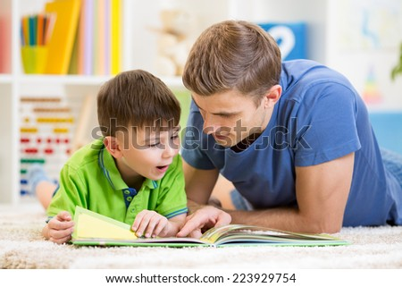 kid boy and his father read a book on floor at home