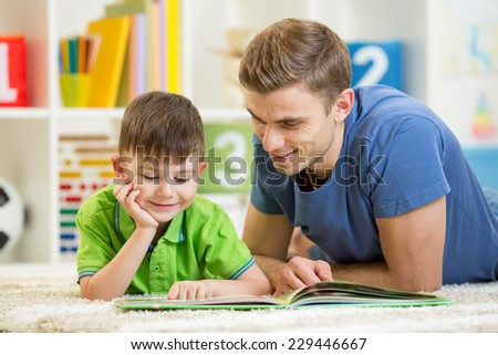 kid boy and his father reading a book on floor indoors