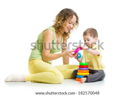 kid boy and mother play together with pyramid toy - stock photo