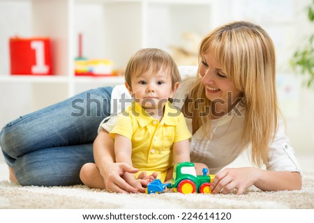 kid boy and woman playing with toy indoor - stock photo