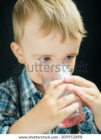 kid boy drinking juice. Studio photo with black background - stock photo