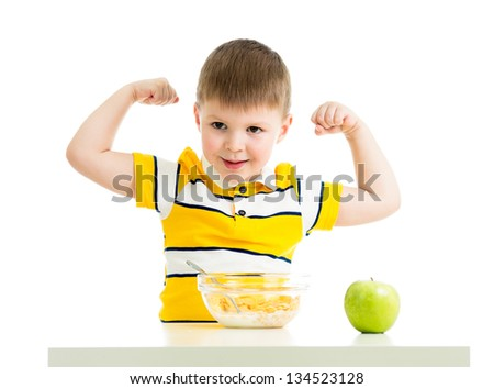 kid boy eating healthy food and showing his strength - stock photo