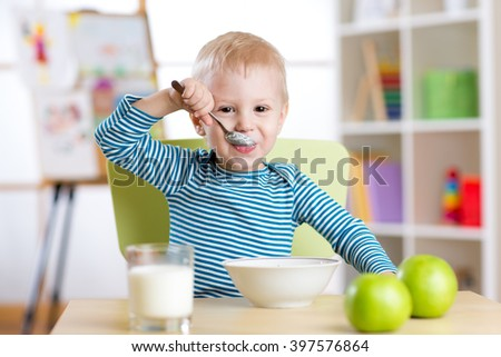 kid boy eating healthy food at home or daycare