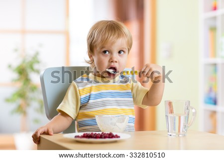 kid boy eating healthy vegetables at nursery room - stock photo