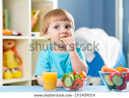 kid boy eating vegetables at home interior