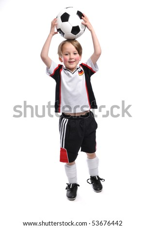 Kid / Boy in complete german soccer outfit holding a football above his head - stock photo