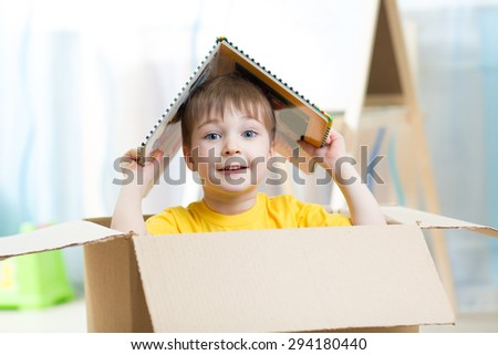 kid boy playing in a toy house in nursery - stock photo