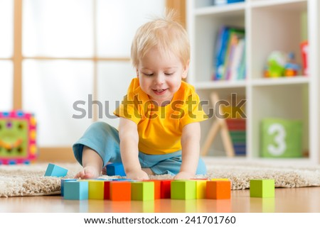 kid boy playing  wooden toys at home or kindergarten - stock photo