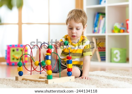 kid boy plays with educational toy indoors - stock photo
