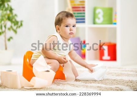 kid boy sitting on chamber pot with toilet paper roll - stock photo