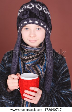 Kid boy wearing winter clothes, holding knitted cup