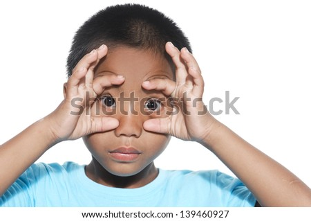 kid boy with funny face and fingers on his eyes