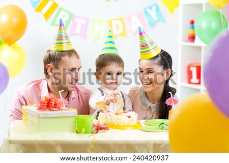 kid boy with parents blow candles on birthday cake