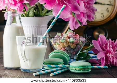 Kid breakfast with milk and macaroons on table with flowers