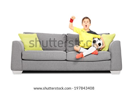 Kid cheering and holding football seated on sofa isolated on white background - stock photo