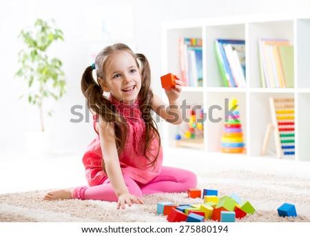 kid child girl playing on floor at nursery or kindergarten - stock photo