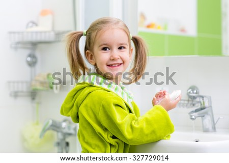 kid child girl washing her face and hands with soap in bathroom - stock photo