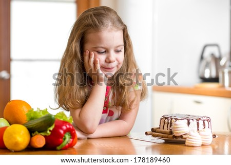 kid choosing between healthy vegetables and tasty sweets - stock photo