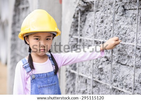 Kid civil engineer inspecting wire mesh on huge concrete pipe wall with bad mood