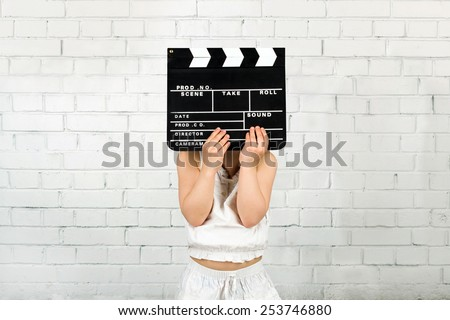 Kid cover face with clapper board against brick wall - stock photo